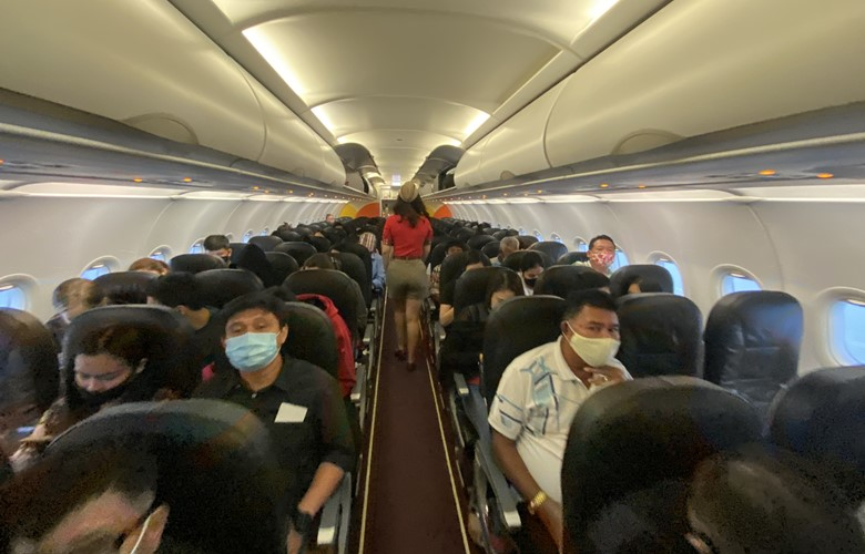 flight attendent leading passengers to seat on a flight during the covid pandemic
